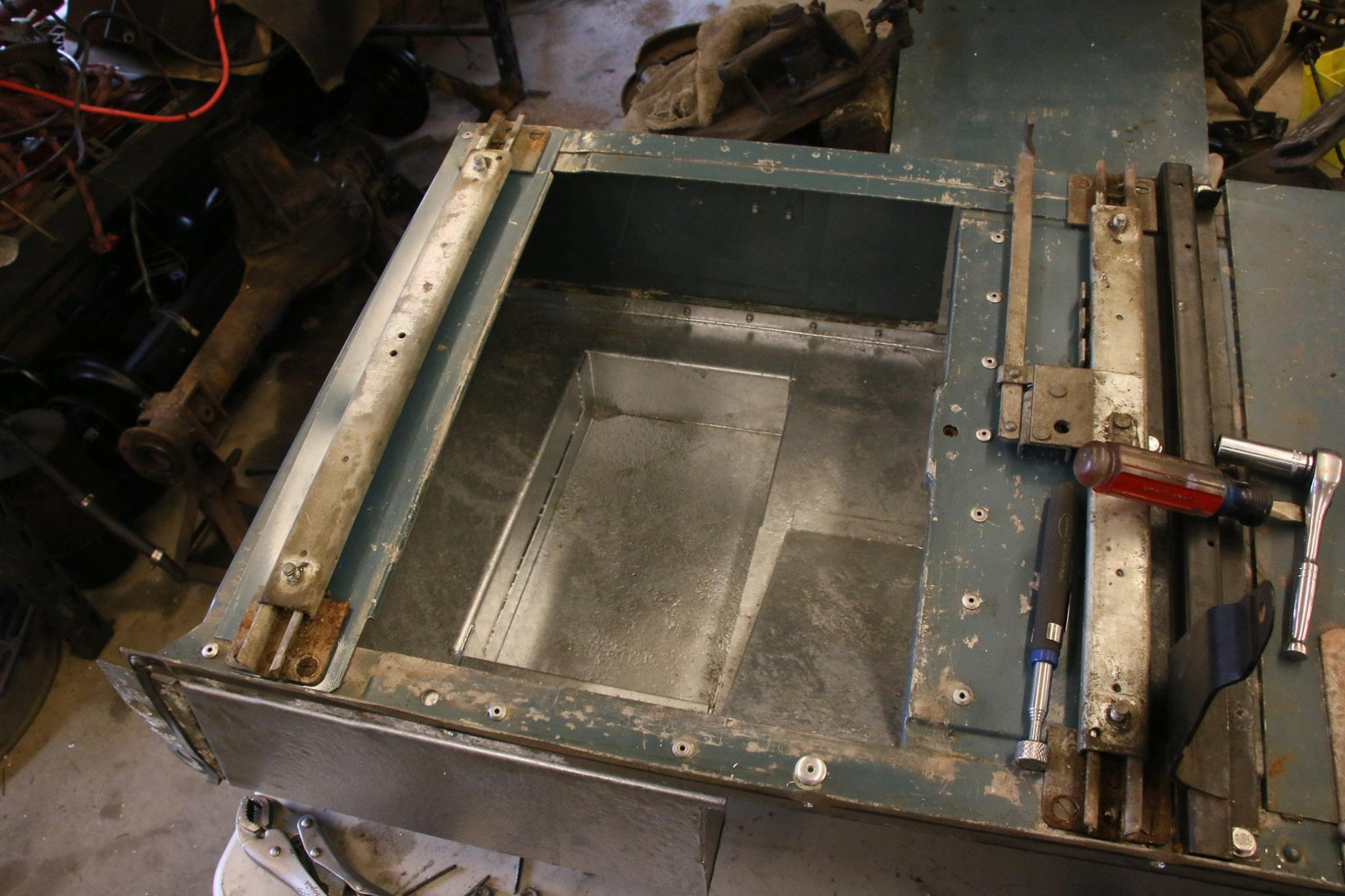 A galvanized under seat box is riveted to the seat box.