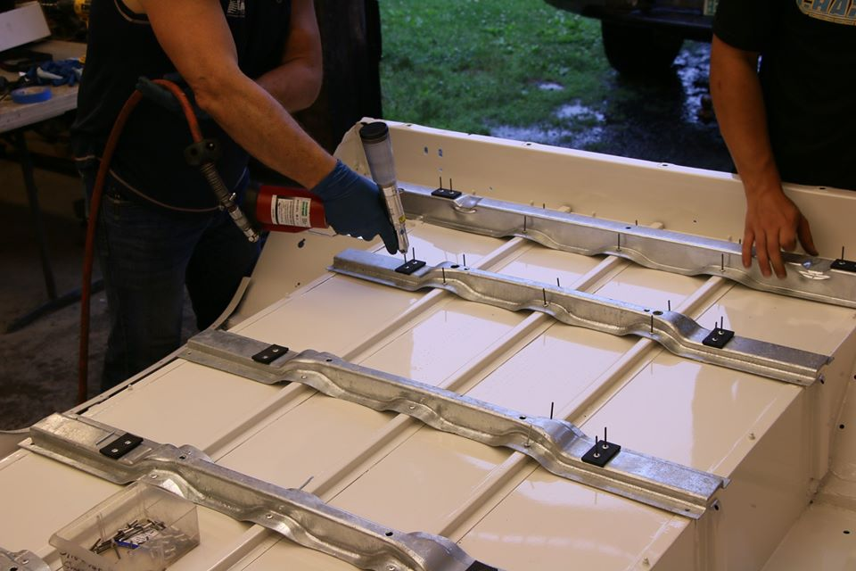Riveting galvanized underbody supports to a freshly painted rear tub.