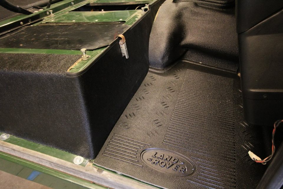 A new genuine Land Rover rubber floor mat and seat box Hardura trim is installed.