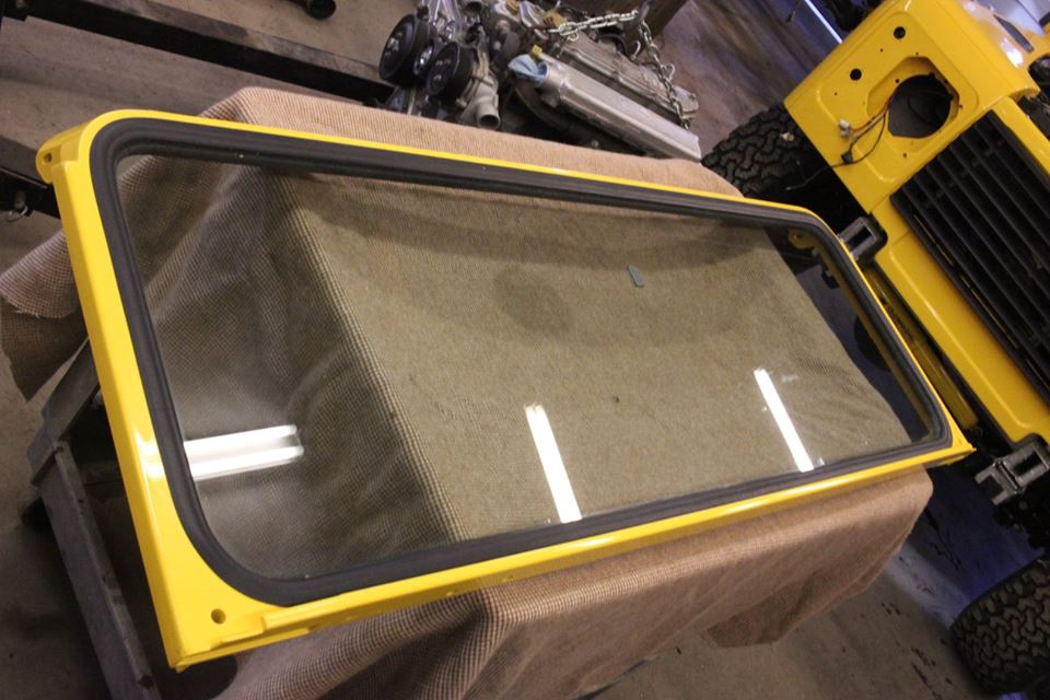 A new windshield is installed in the repainted frame with a new genuine Land Rover gasket.